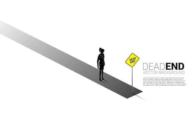 Empresária de silhueta em pé com sinalização de beco sem saída. conceito de decisão errada nos negócios ou fim da carreira.
