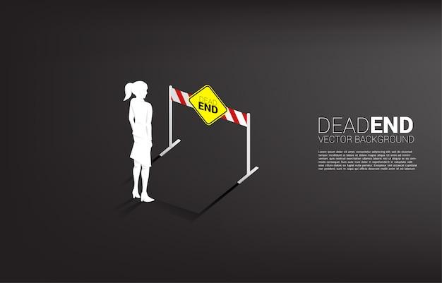 Empresária de silhueta em pé com sinalização sem saída. conceito de decisão errada nos negócios ou no final da carreira.