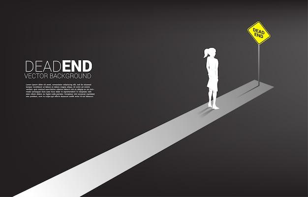 Empresária de silhueta em pé no final da estrada com sinalização sem saída. conceito de decisão errada nos negócios ou no final da carreira.
