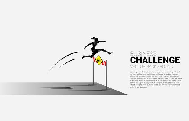 Empresária de silhueta pulando obstáculo de barreiras sem saída. conceito de plano de fundo para obstáculo e desafio nos negócios