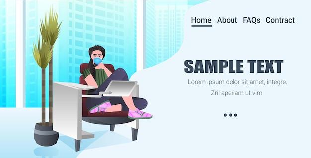 Empresária na máscara sentada no local de trabalho e usando o laptop coronavirus pandemia conceito moderno escritório interior horizontal