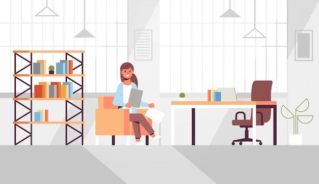 Empresária, sentado na mesa de trabalho, mulher de negócios, segurando os documentos em papel, preparando o relatório, trabalhando o processo moderno escritório interior