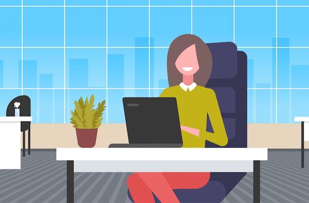 Empresária, sentado na mesa de trabalho, mulher de negócios usando o laptop trabalhando processo conceito moderno escritório interior retrato horizontal