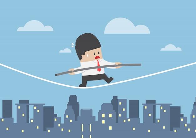 Empresário andando em uma corda sobre a cidade