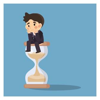 Empresário continue sentado e esperando em uma ampulheta