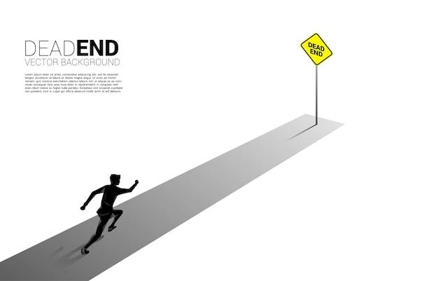 Empresário de silhueta correndo para o fim da estrada com sinalização de beco sem saída. conceito de decisão errada nos negócios ou fim da carreira.