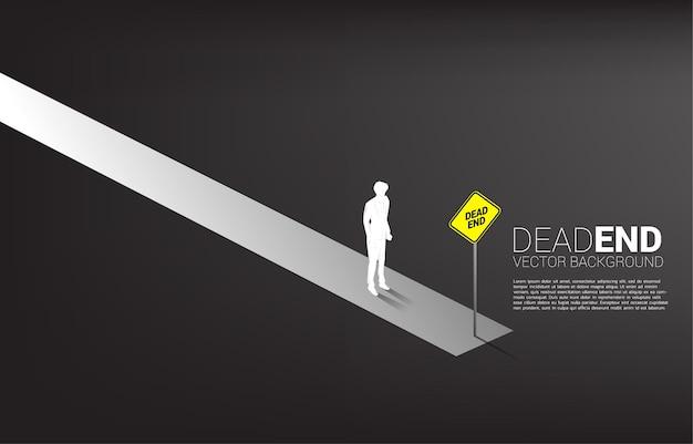 Empresário de silhueta em pé no final da estrada com sinalização de beco sem saída.