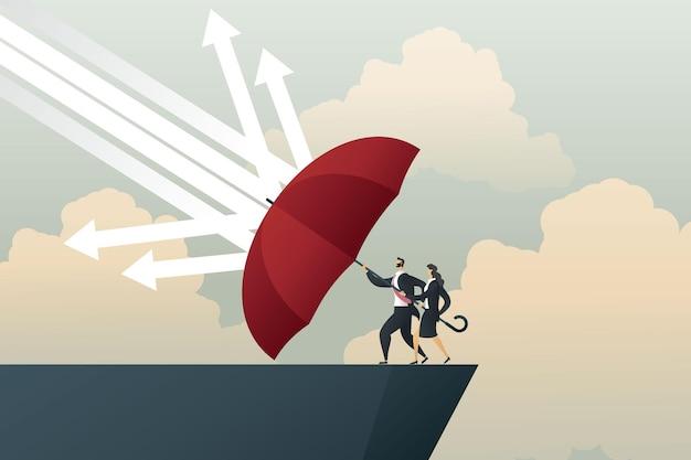 Empresário e empresária com guarda-chuva vermelho protegem as flechas da chuva caindo no penhasco