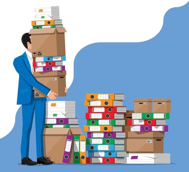 Empresário e pilha de pastas de escritório, documentos.