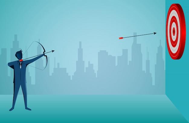 Empresário em pé atirando uma flecha para o alvo no centro do círculo vermelho.