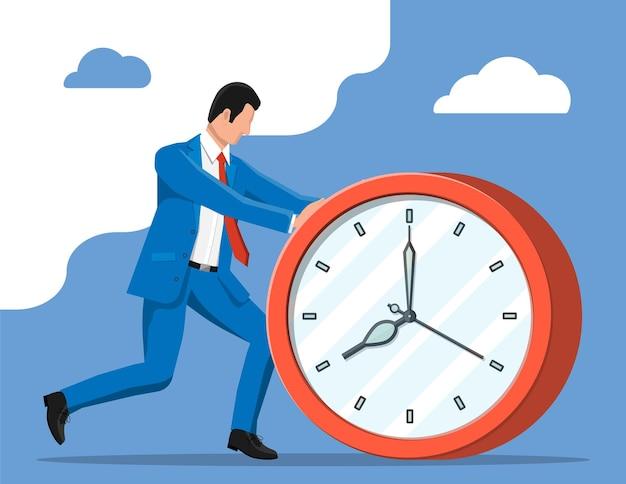 Empresário empurrando um grande relógio