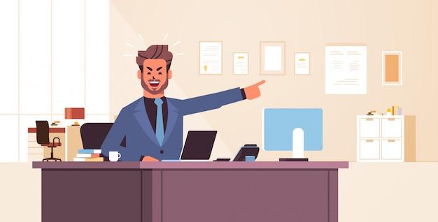 Empresário irritado, sentado no local de trabalho, apontando o dedo na porta