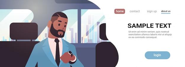 Empresário, olhando o relógio, verificando o tempo, passageiro sentado no banco de trás no táxi cidade transporte serviço conceito retrato horizontal cópia espaço