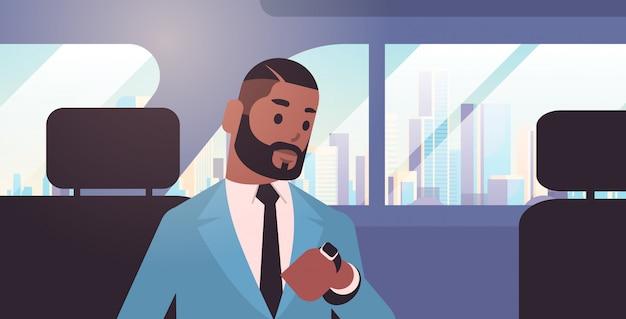 Empresário, olhando o relógio, verificando o tempo, passageiro sentado no banco de trás no táxi cidade transporte serviço conceito retrato horizontal