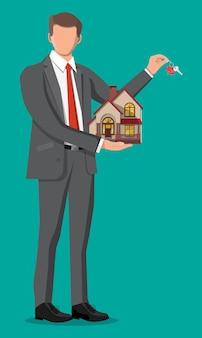 Empresário segurando a chave e a construção da casa