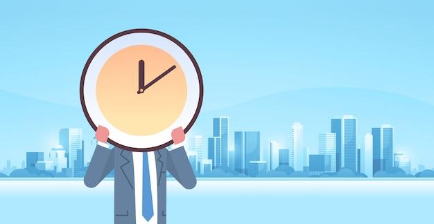 Empresário, segurando, relógio, frente, tempo eficaz, gerência prazo, conceito negócio, eficiência, modernos, cidade, edifícios, cityscape, fundo, horizontal, macho, personagem, retrato