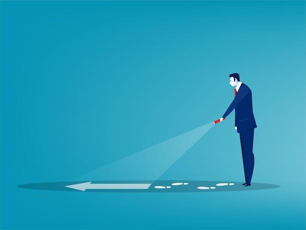 Empresário segurando uma lanterna e descobrindo um sinal de seta