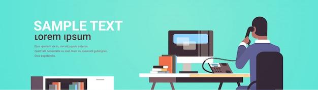 Empresário sentado na mesa de trabalho vista traseira homem de negócios usando o computador enquanto fala no telefone fixo trabalhando conceito de processo retrato horizontal espaço de cópia