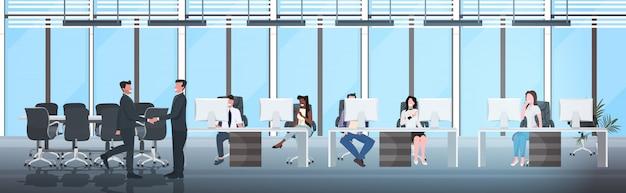 Empresários, apertando as mãos, sentado nos locais de trabalho
