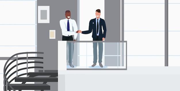 Empresários, apertando mãos, misture, raça, sócios, handshaking, durante, reunião, acordo, parceria, conceito, modernos, escritório, interior