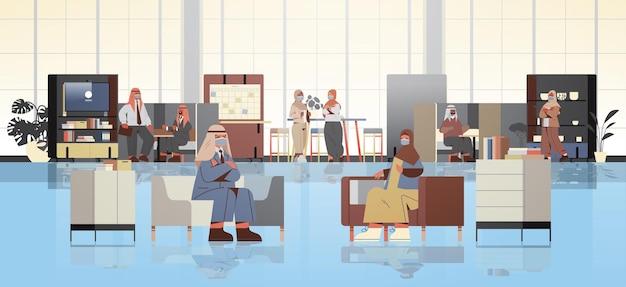 Empresários árabes mascarados discutindo durante a reunião no conceito de pandemia de coronavírus de coworking criativo