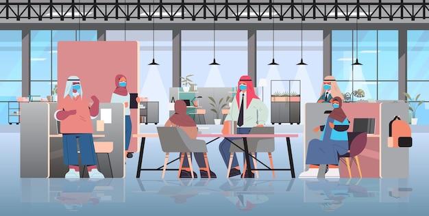 Empresários árabes mascarados discutindo durante a reunião no conceito de trabalho em equipe de pandemia de coronavírus de centro de coworking criativo