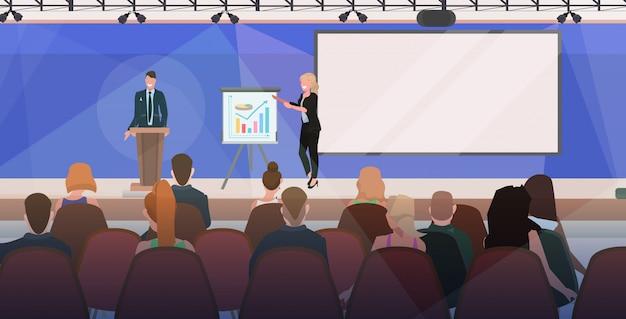 Empresários casal tribuno discurso empresários fazendo apresentação financeira na reunião da conferência com flip chart sala de reuniões moderna interior plana horizontal