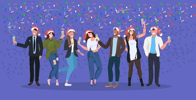 Empresários com chapéus de papai noel com confete festa corporativa empresários comemorando feliz natal feliz ano novo férias de inverno conceito