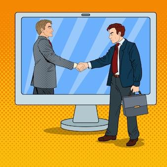 Empresários de arte pop apertam as mãos na tela do computador. contrato comercial.