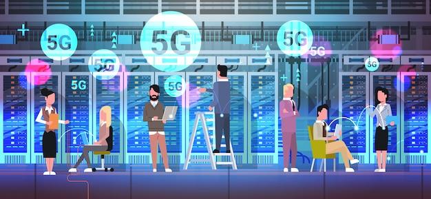 Empresários trabalhando juntos na sala do centro de dados que hospeda o servidor 5g conexão do sistema sem fio on-line monitoramento de computador informações banco de dados comprimento total horizontal