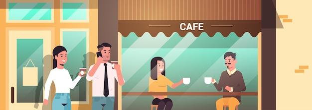 Empresários visitantes fazendo pausa para o café homens mulheres bebendo bebidas quentes moderno café de rua retrato exterior
