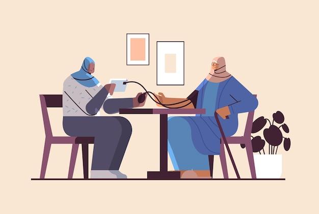 Enfermeira árabe ou voluntária verificando a pressão arterial de pacientes idosas, mulheres árabes, serviços de atendimento domiciliar à saúde