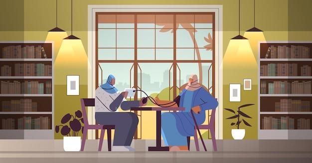 Enfermeira ou voluntária árabe amigável verificando a pressão sanguínea para uma mulher idosa, paciente, serviços de cuidados domiciliares, serviços de saúde e apoio social conceito de apoio social interior de lar de idosos horizontal comprimento total vector illustrat