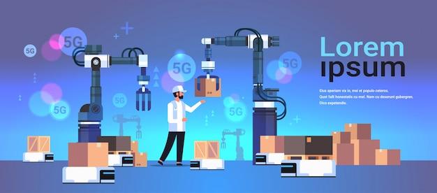 Engenheiro, controlando as mãos robóticas, colocando caixas na entrega do robô