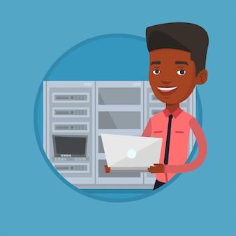 Engenheiro trabalhando no laptop na sala de servidores de rede.