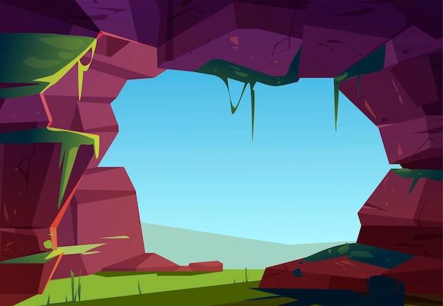 Entrada para caverna na montanha, buraco na rocha com grama verde, musgo e vista do céu azul