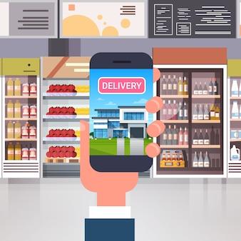 Entrega dos produtos da loja com mão usando o telefone esperto sobre o conceito interior da compra da ordem do mantimento do supermercado