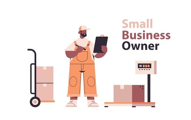 Entregador afro-americano uniformizado verifica as encomendas em um armazém de logística de carga de entrega expressa ou conceito de serviço postal
