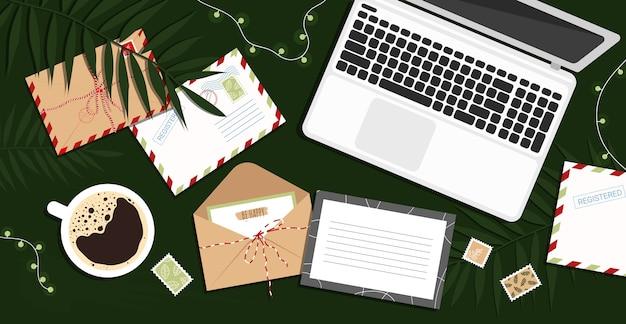 Envelope, carta, cartões postais e laptop na mesa. local de trabalho com computador e cartões, uma xícara de café em estilo simples