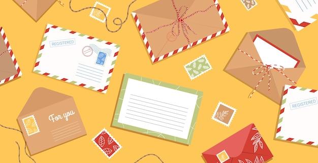 Envelope, cartas, selos e cartões postais na mesa.