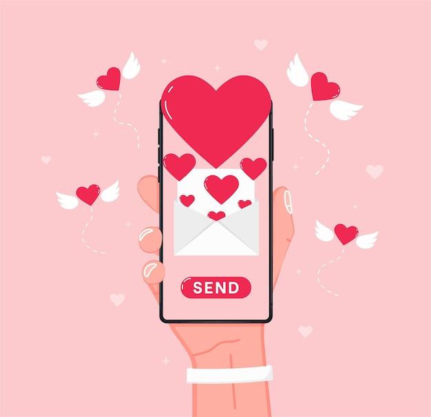 Enviando mensagem de amor com a mão segurando o celular com um coração de amor na tela