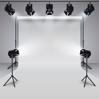 Equipamento de iluminação e fundo em branco branco do estúdio profissional da fotografia.