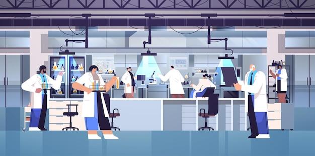 Equipe científica de pesquisa de raça mista trabalhando com pesquisadores de tubos de ensaio fazendo experimentos químicos em laboratório