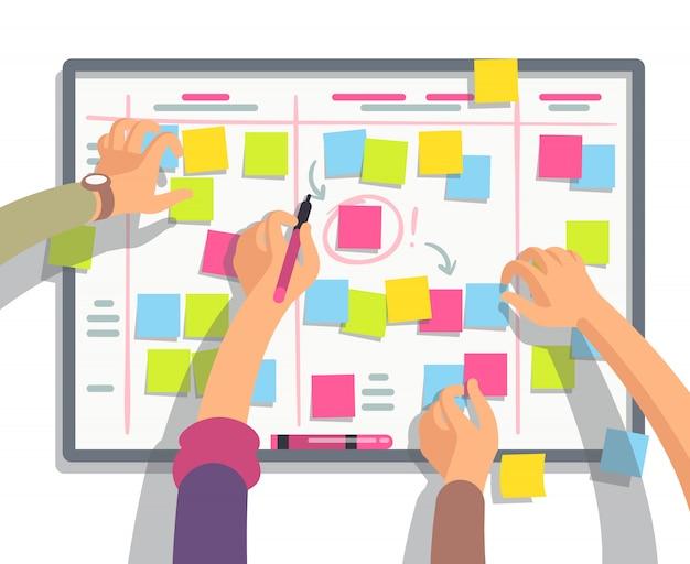 Equipe de desenvolvedores planejando tarefas de agendamento semanal no quadro de tarefas.