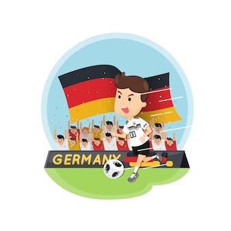 Equipe de jogador de futebol do alemão em uniformes brancos e pretos com fundo de fãs.