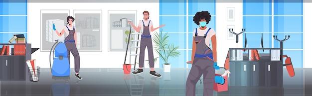 Equipe de limpeza profissional mistura zeladores de corrida com equipamento de limpeza trabalhando juntos interior de escritório horizontal