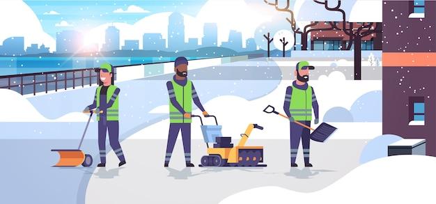 Equipe de limpeza usando diferentes equipamentos e ferramentas remoção de neve conceito mistura raça homens mulheres de uniforme limpeza área residencial urbana paisagem plana comprimento total ilustração vetorial horizontal