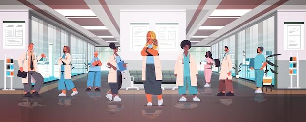 Equipe de médicos de corrida mista uniformizados, juntos no corredor do hospital, medicina, conceito de saúde, ilustração vetorial de corpo inteiro horizontal