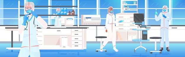 Equipe de médicos segurando tubos de ensaio com células de coronavírus, amostra de desenvolvimento de vacina contra covid-19