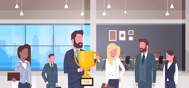 Equipe de negócios bem sucedidos com chefe segurando a taça de ouro, grupo de empresários vencedores juntos em m